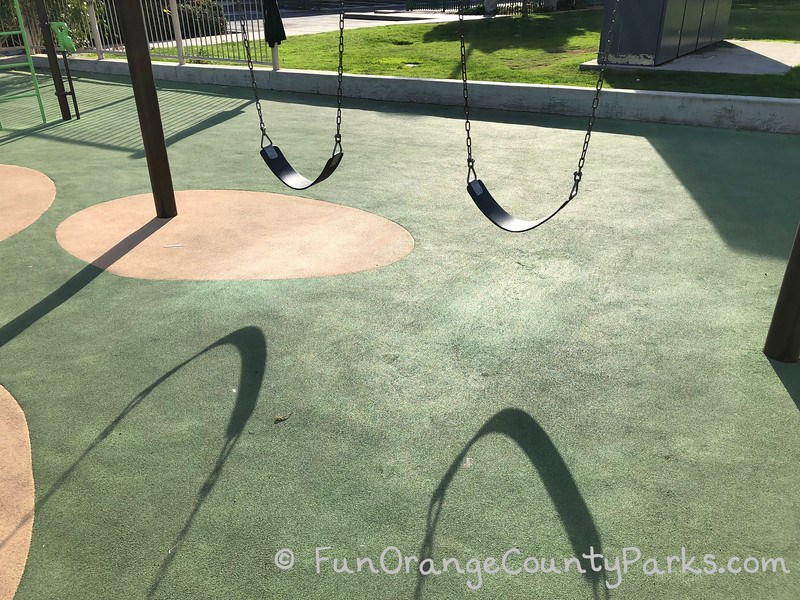 bench swings in sun with shadow on playground