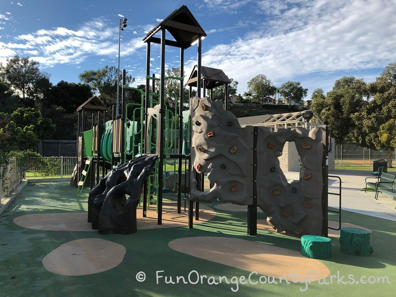 green playground with view of climbing wall