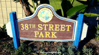wooden sign with city of newport beach seal and 38th street park written in yellow text