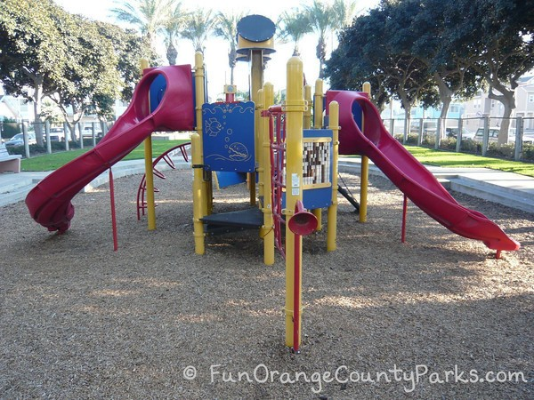 38th Street Park playground with red slides on either side with yellow and blue on a bark play surface