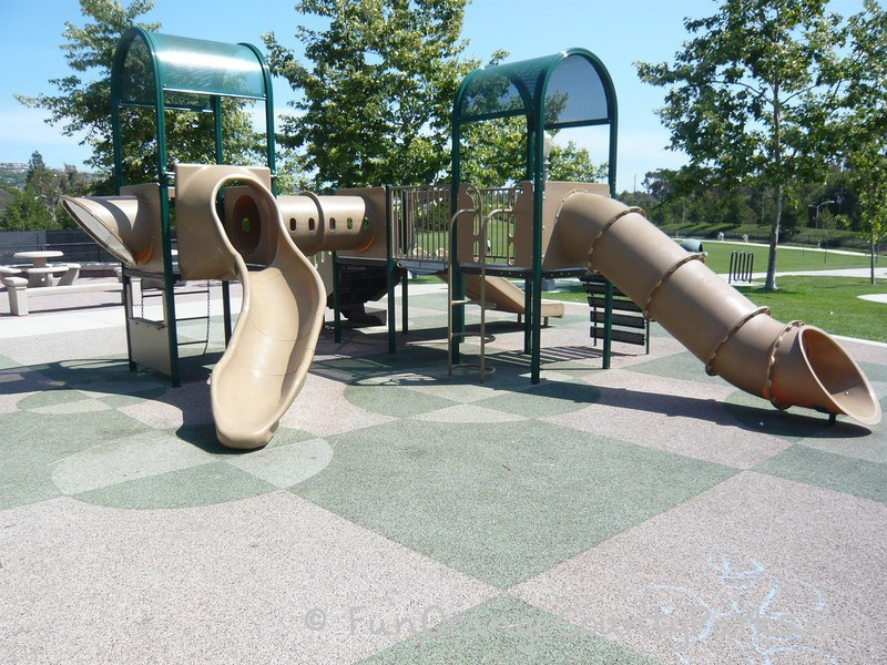 tunnel slide and slightly curved slide on recycled rubber surface