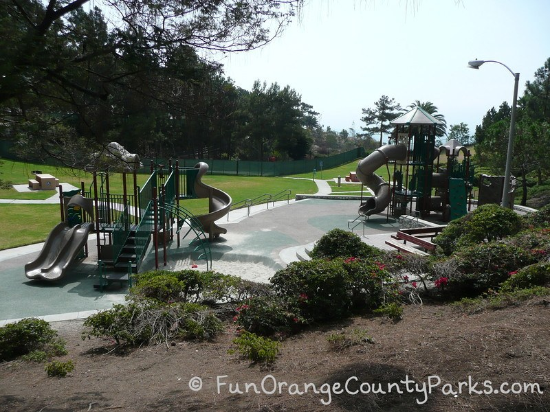 Pines Park playground with 2 play structures visible on recycled rubber pad with picnic tables and a grassy area