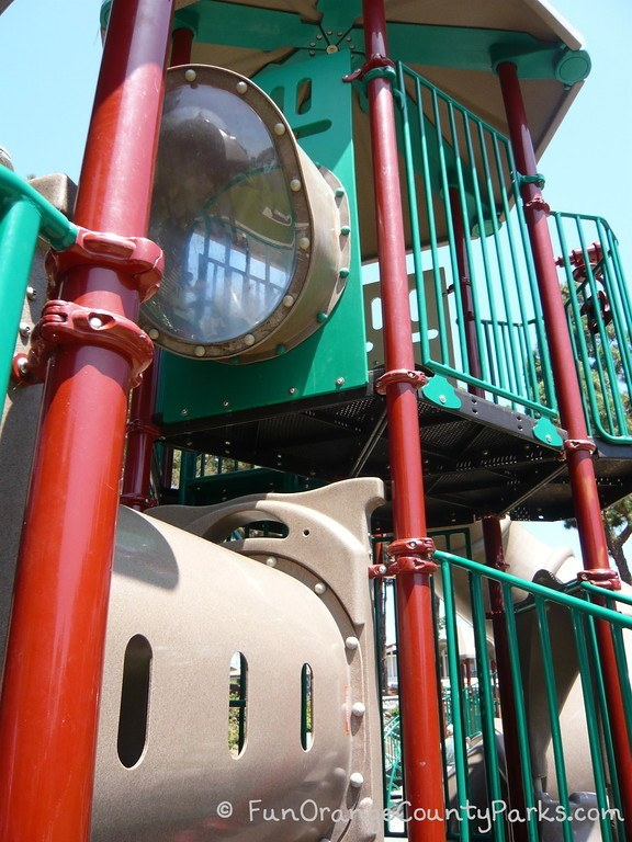 green and rust colored playground with up-close view of 2 story play structure at Pines Park