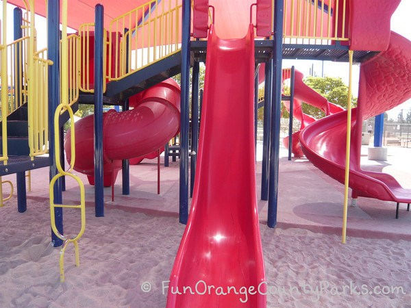 straight red slide with three more slides in the back ground under a red shade cover at Tustin Sports Park playground