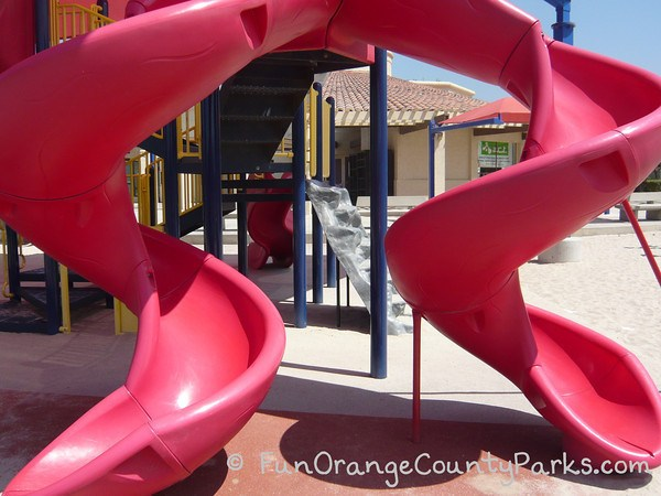 two red twisty slides with sand play surface and a building in the background at Tustin Sports Park playground