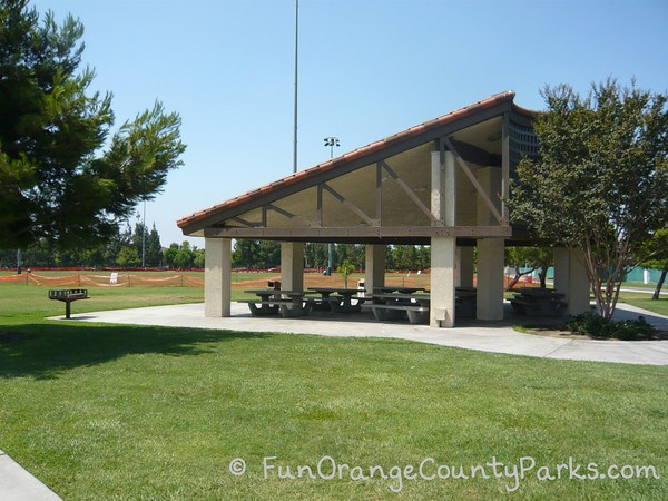 large covered picnic shelter with a grill and surrounding lawn area at Tustin Sports Park