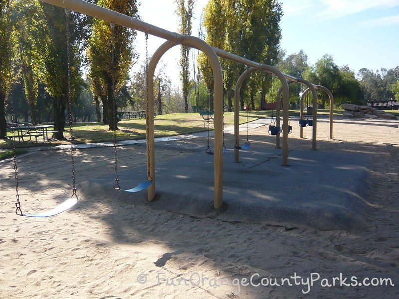 swings over sand and recycled rubber pad