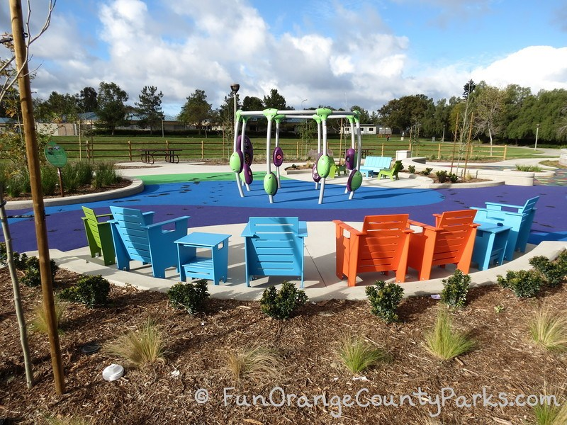 pavion park dance play area with colorful chairs surrounding circular dance floor area with equipment that plays songs