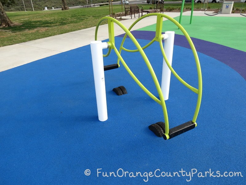 Standing teeter totter equipment at Pavion Park in Mission Viejo. Bright green bars on a blue recycled rubber surface.