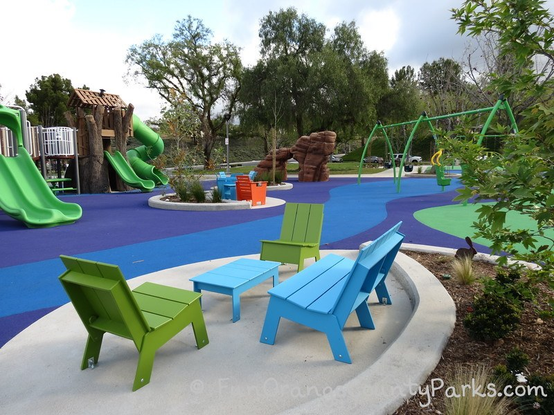 blue bench and table with 2 green chairs with view of playground and rock climbing structure in the middle of Pavion Park in Mission Viejo