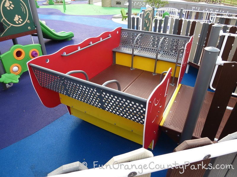 boat play equipment with entry wide enough for wheelchair which rocks back and forth when pushed by friends