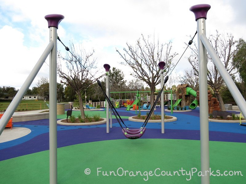 zip track swing in foreground with full playground in the background