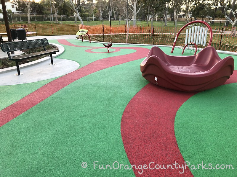 merry-go-round and music panels on green and red recycled rubber surface