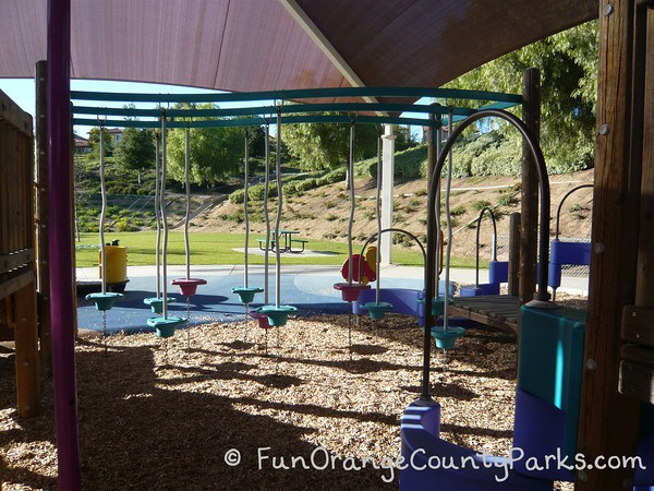 playground under shade cover with pedestals for navigating over a bark surface at Fullerton Sports Complex