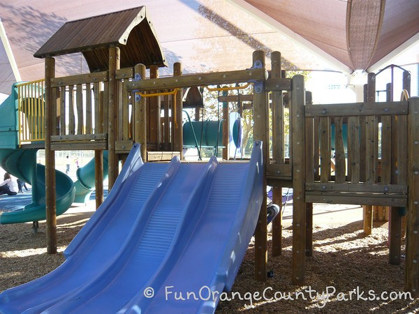 blue colored triple slide with what appears to be a wooden clubhouse on a the wooden playground platform at Fullerton Sports Complex playground