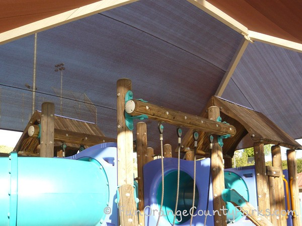 view of the top of the playground structure with blue plastic tunnels and a huge shade cover at Fullerton Sports Complex playground