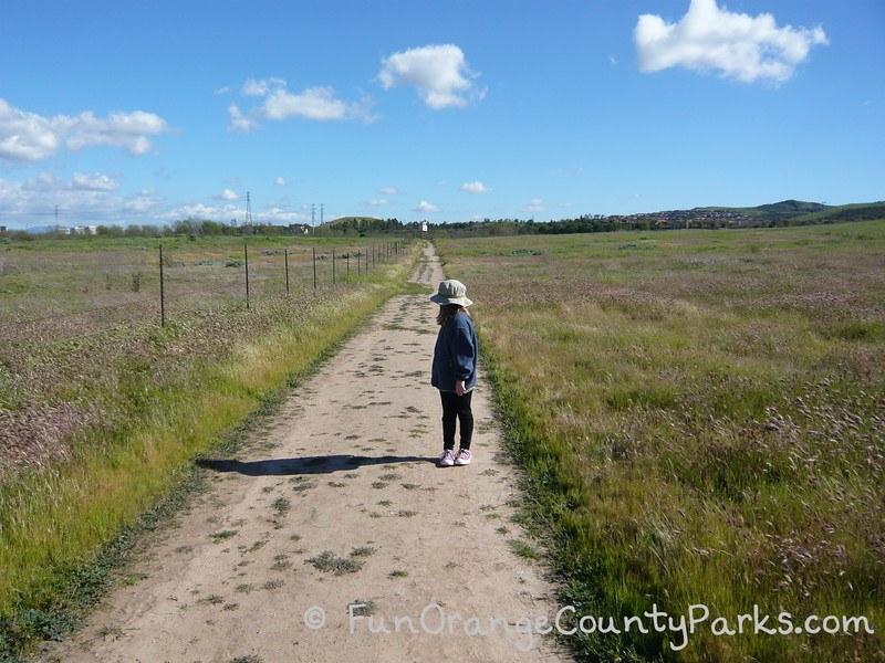 Quail Hill Loop Trail with girl wearing jeans and hat surrounded by green grass and blue sky