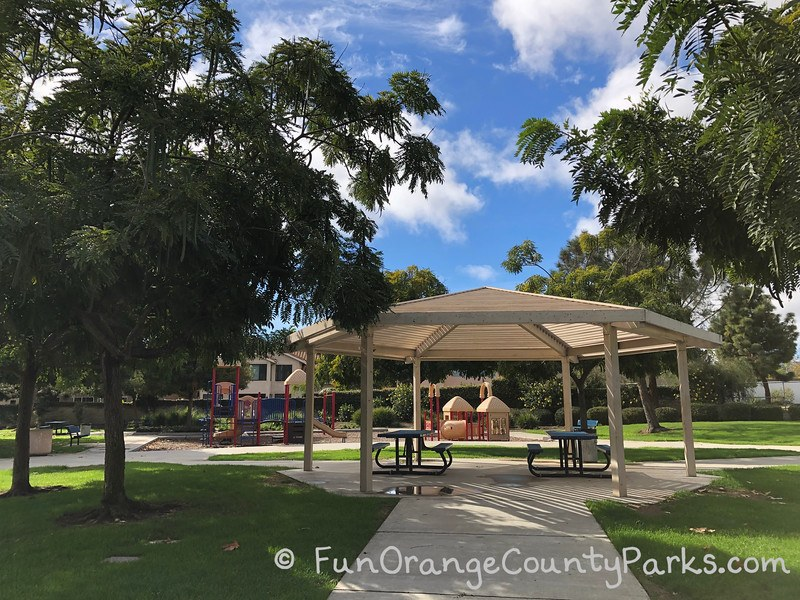 Ocean Breeze Park gazebo in a lush green area with trees and blue sky above.