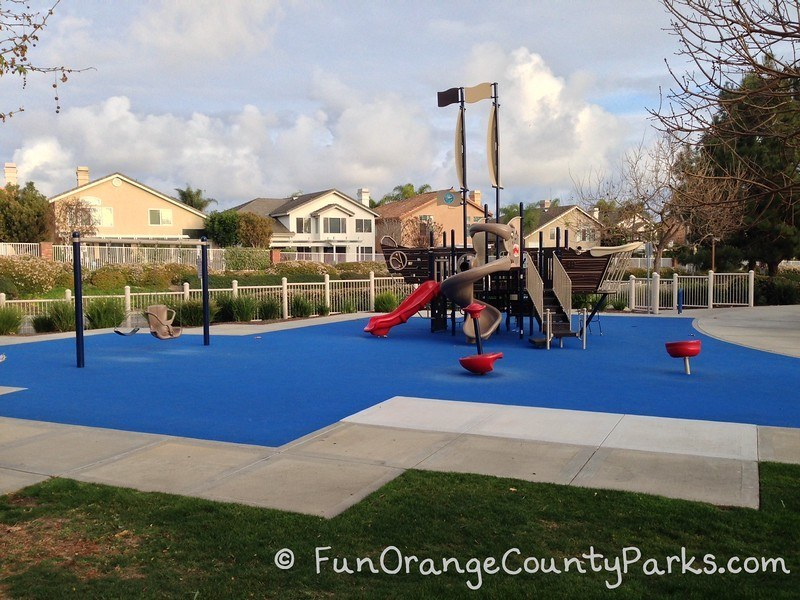 Ocean Breeze Park in Laguna Niguel with  red spinners and a pirate ship playground on a blue recycled rubber play surface. Swingset with chair swing and bench swing also visible.