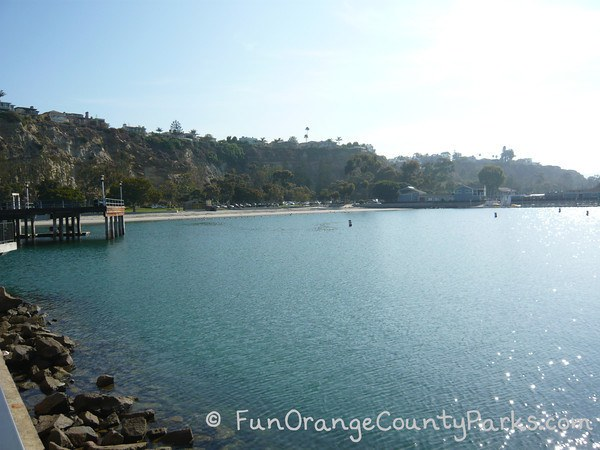 View of Baby Beach at Dana Point Harbor with ocean in foreground and a thin strand of beach along bluffs