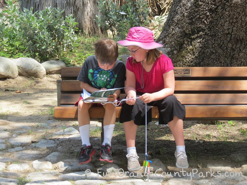 boy and girl sitting on bench with a scavenger hunt and pens
