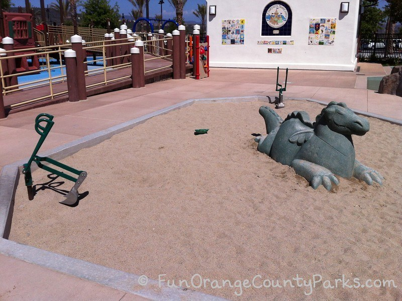 sand area with sea monster sculpture and digger at Courtney's Sandcastle Accessible Playground San Clemente