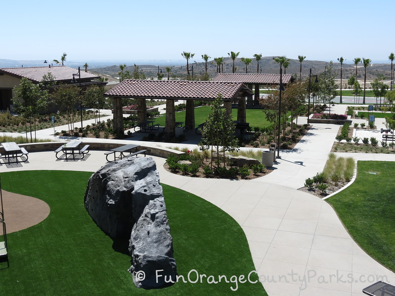 aerial view of picnic area at Baker Ranch Community Park with two shelters that have red tile roofs and a lawn area between them - a big climbing boulder sits below on the playground