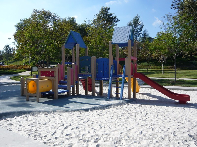 Smaller playground with tunnels and blue roof with red slides