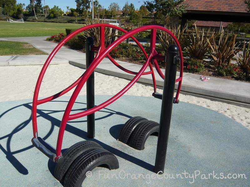 Red stand on teeter totter on sand play surface