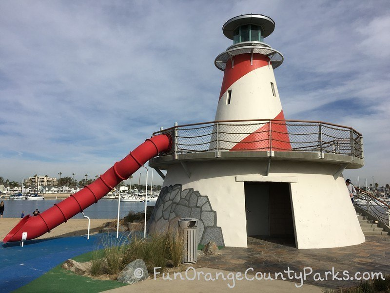 Marina Park bathroom building with a lighthouse on top and red tunnel slide