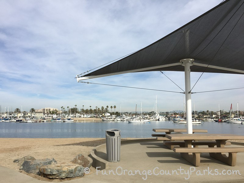 picnic shelter and shade at beach with sand and harbor view