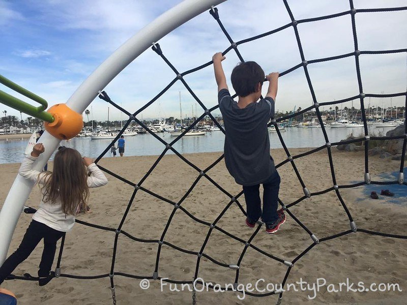 little girl and little boy on spiderweb play structure with sand and harbor view