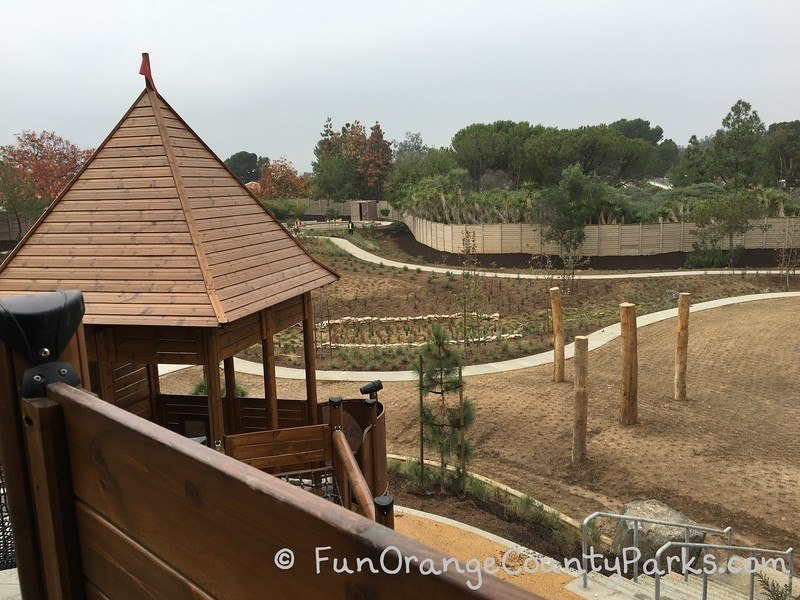 wooden play structure tower on left of photo showing overview of dirt playground area
