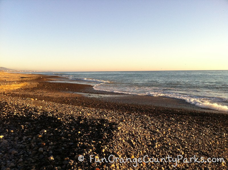 parks and beaches parking passes - capistrano beach rocks and ocean waves along the shoreline at sunset