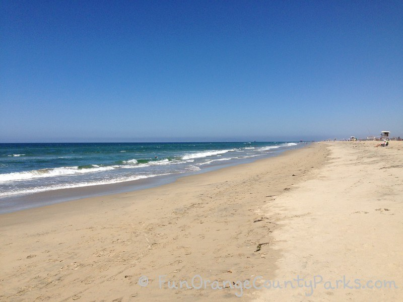 parks and beaches parking passes - huntington beach with wide white sand and green blue ocean