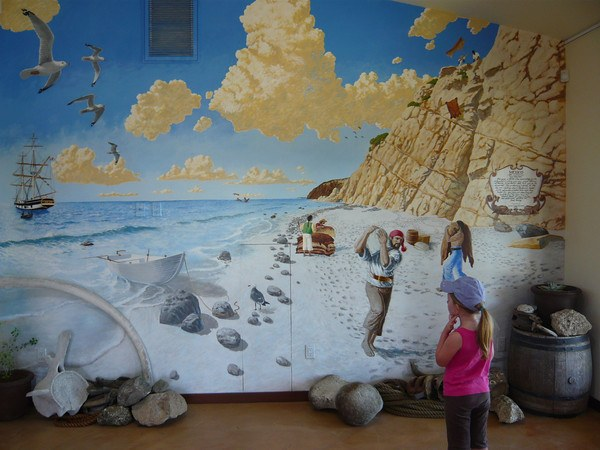 young girl with a pink shirt and purple cap looking at mural of pirates on the beach below the bluff at Dana Point Headlands