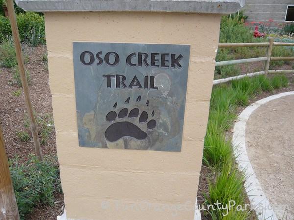 oso creek trail sign with bear print on concrete column