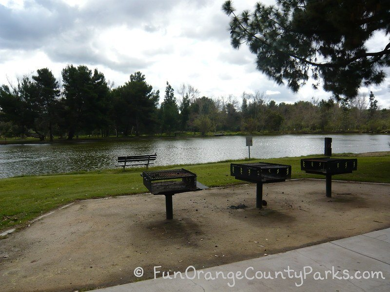 three large barbecue grills and a bench lakeside at Yorba Regional Park