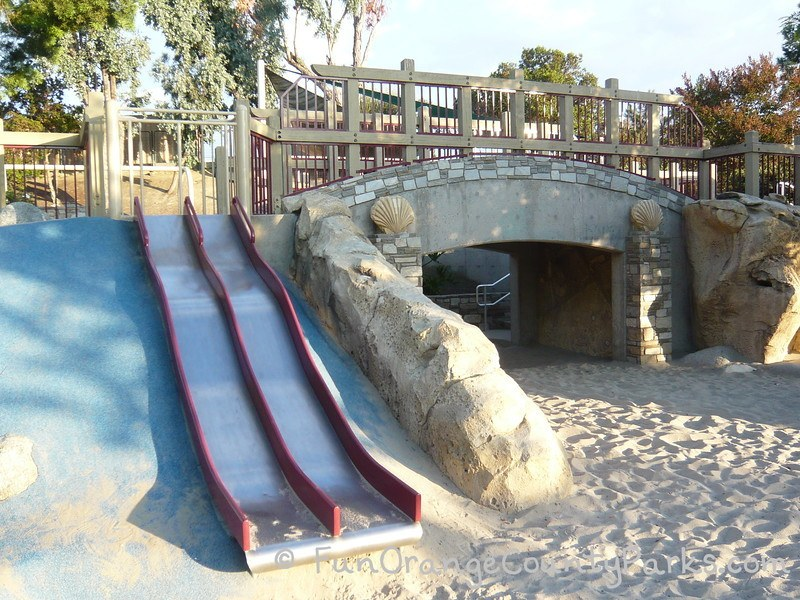 Dino Park in Laguna Hills view of metal slides and tunnel with fossils