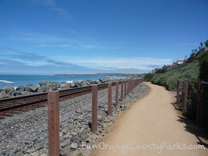 San Clemente Beach Trail with its dirt path down the center of the photo with the ocean and train tracks on the left with a green hillside on the right. A blue sky day with Dana Point Harbor visible in the distance.