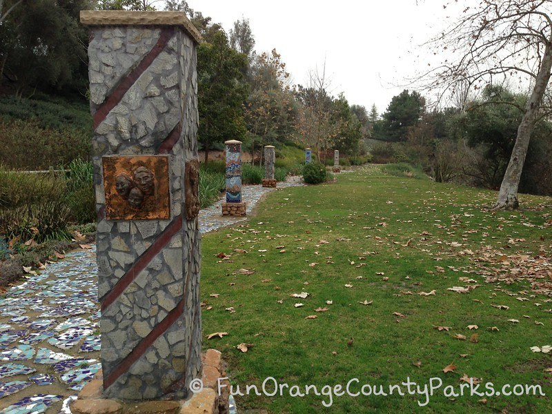 Five columns designed with mosaics of rock and tile along the Oso Creek Trail in Mission Viejo with a grassy area and sycamore tree.