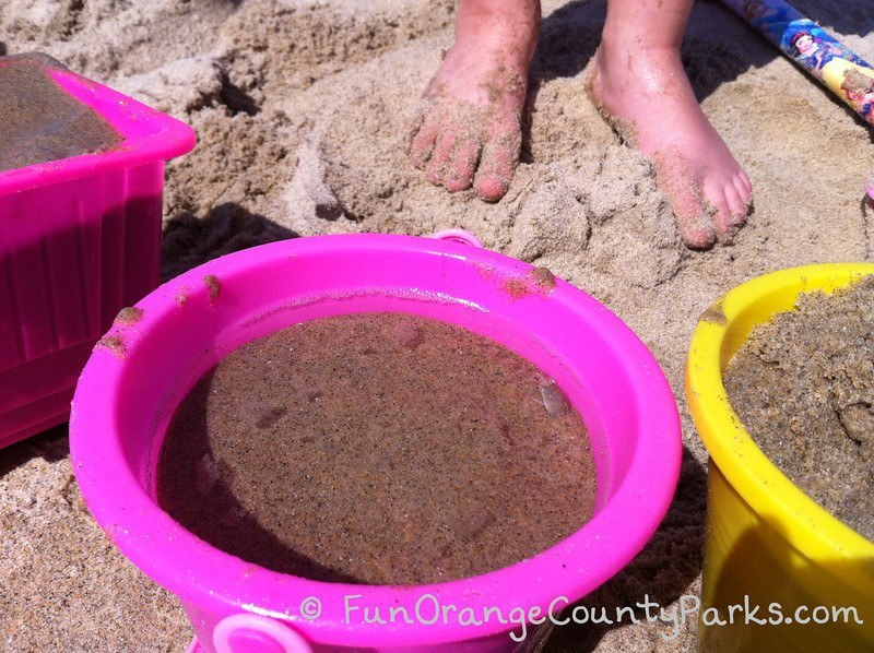 bare feet and sand toys