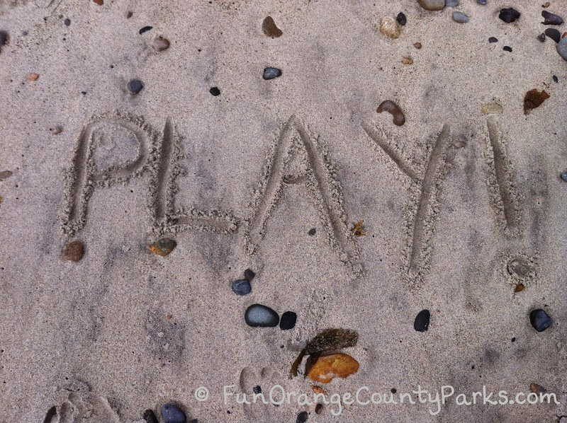 the word play written in the sand at the beach