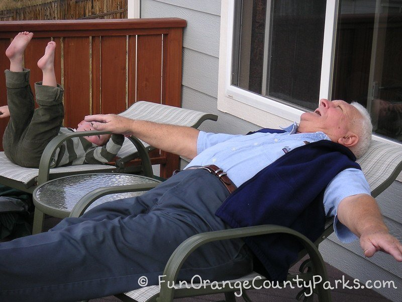 grandpa and little boy pretending they are flying while reclining in chairs