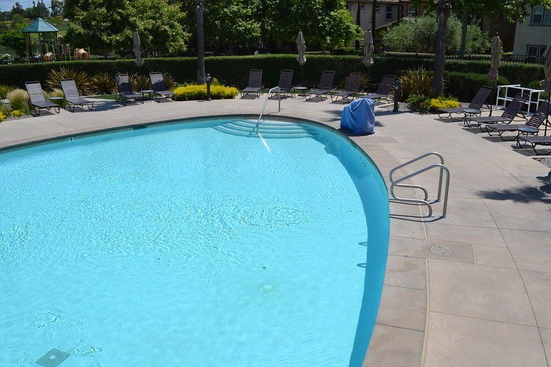 half of an oval-shaped pool with brown lounge chairs at the Aliso Viejo Aquatic Center