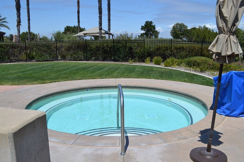 round concrete in-ground spa with lawn area nearby