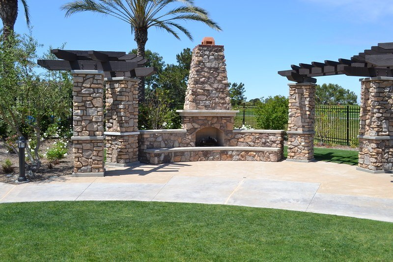stonework for outdoor fireplace with arbors on either side for photos