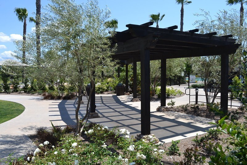 shaded area covered by a dark wood shade cover over concrete