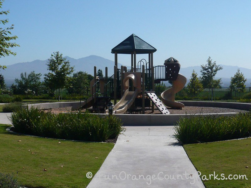 small playground encircled by short 1-foot concrete wall