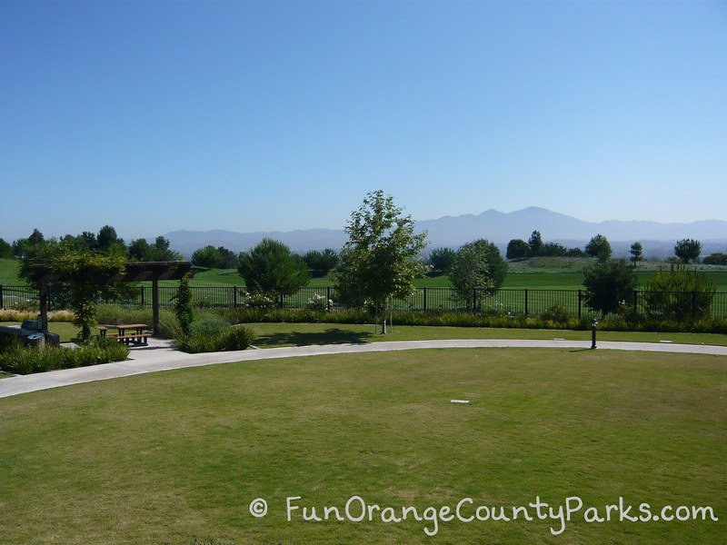 lawn area outside the Aliso Viejo Aquatic Center with a shaded picnic area and golf course visible past a fence